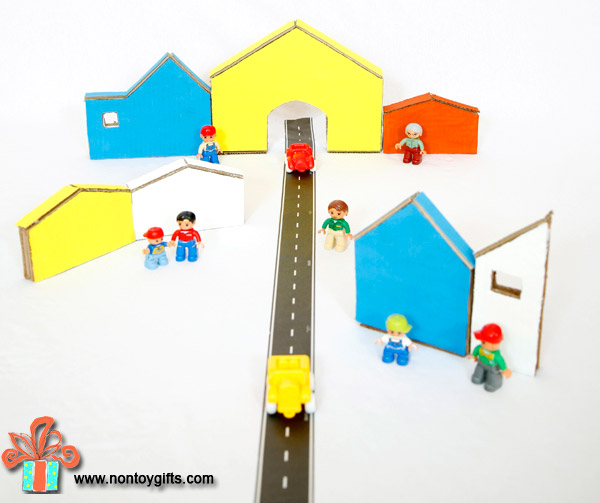 Make a fun and colorful cardboard toy for kids. A cardboard town will keep kids busy for hours. Indoor activity | at Non Toy Gifts