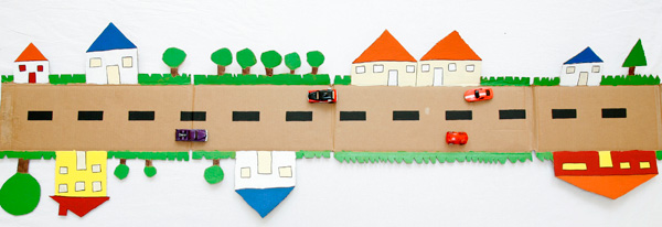 A cardboard road made from a box is a fun DIY toy for kids. Cut out trees and houses on the outer edges and paint them in vibrant colors. | at Non Toy Gifts