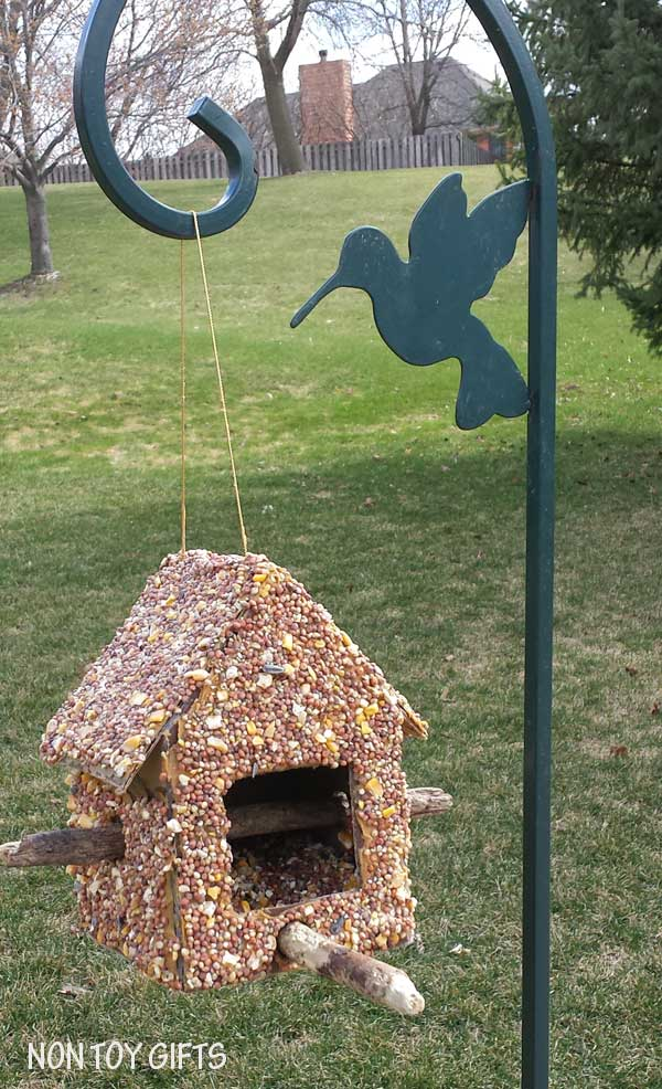 This DIY bird feeder is a fun spring or summer craft to make with kids. You only need a cardboard box, a hot glue gun, two sticks, peanut butter and seeds.