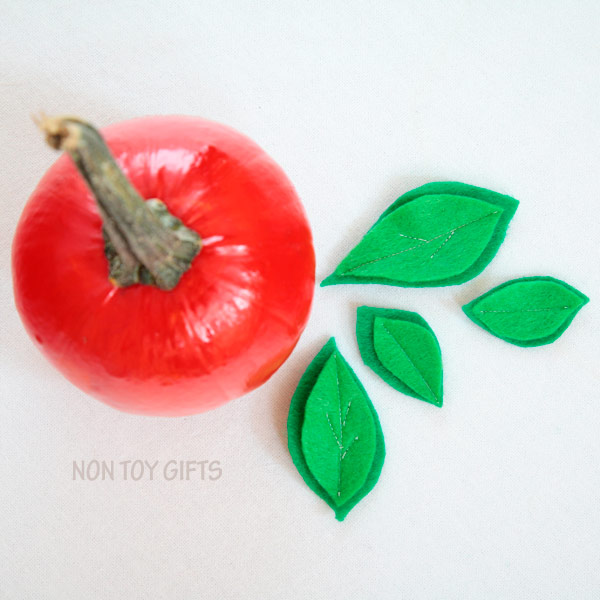 Easy apple pumpkin craft for kids. Perfect fall craft for toddlers or older kids. Paint small pumpkins red and glue a few green leaves. | at Non Toy Gifts