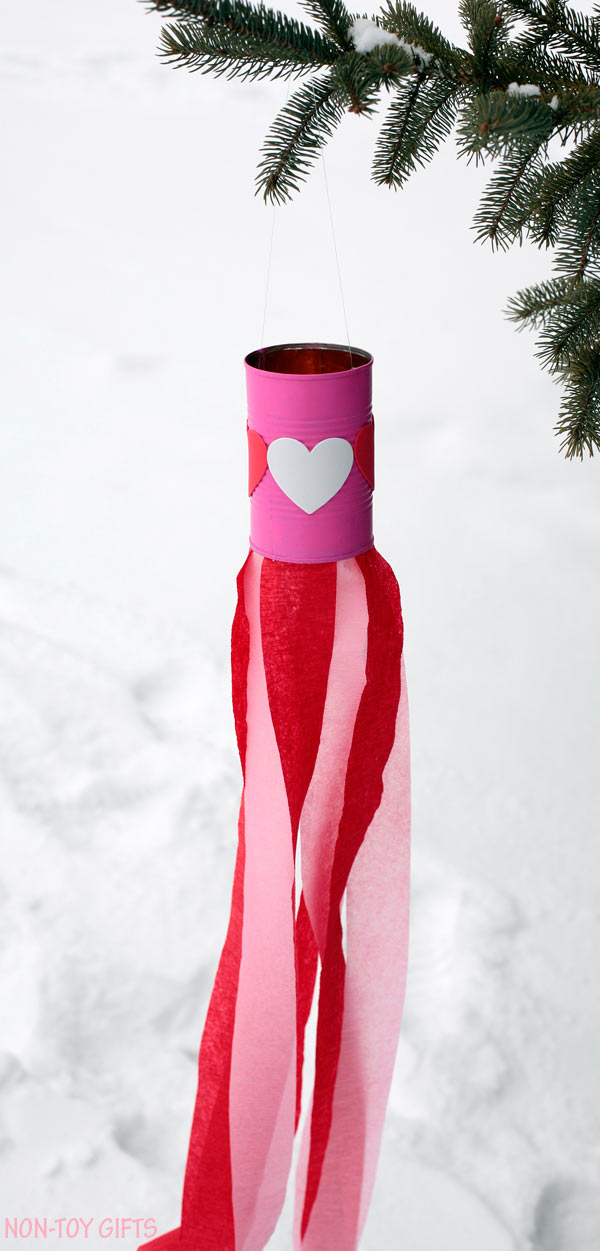 Valentine easy kids craft: heart windsocks. Use tin can, heart stickers, paint and crepe streams to make this DIY Valentine's Day decoration. Perfect craft for preschool or kindergarten. | at Non-Toy Gifts