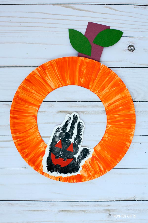 Paper plate Jack'O'Lantern craft for kids. Handprint pumpkin